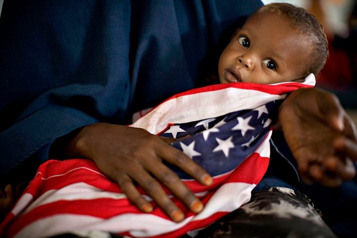 """A malnourished Somali child is wrapped in an American """"Stars and Stripes"""" cloth at a therapeutic feeding center at Dagahaley camp"""
